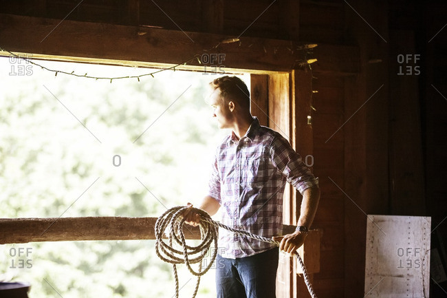Man looking away while holding lasso in stable