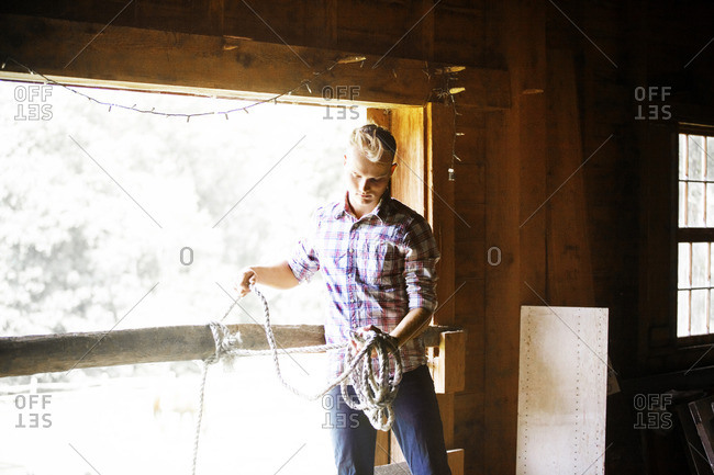Rancher tying lasso on railing in stable