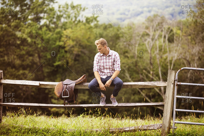Man looking at saddle while sitting on railing in farm