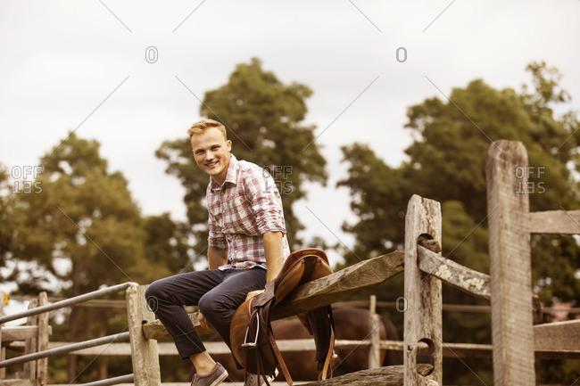 Portrait of rancher sitting on railing against sky