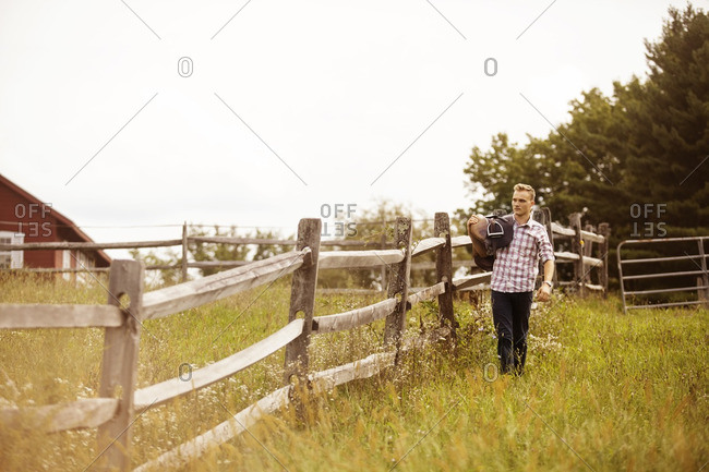 Rancher carrying saddle while walking by fence on grassy field