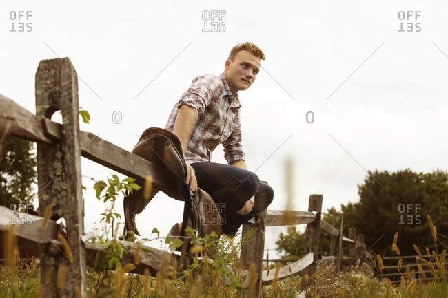 Low angle view of rancher sitting on wooden fence against sky