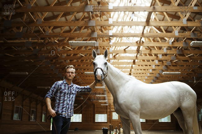 Rancher and horse in stable