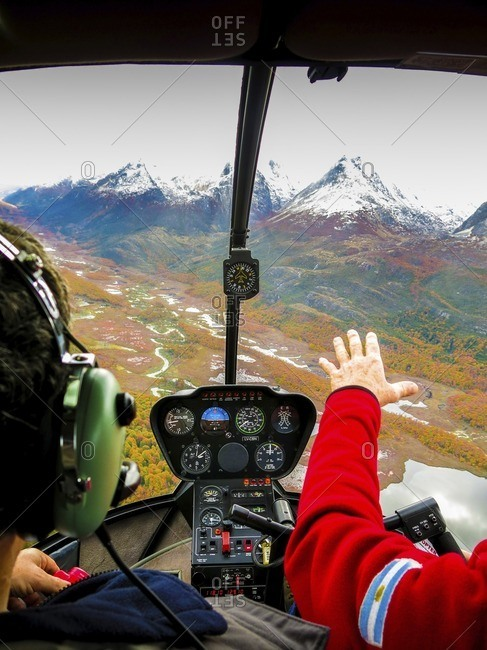 Cropped image of man with pilot in helicopter flying over landscape