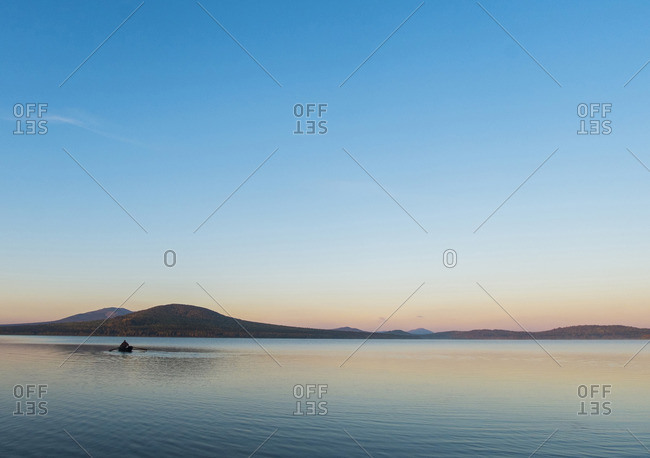 Distant view of man rowing boat on lake against blue sky