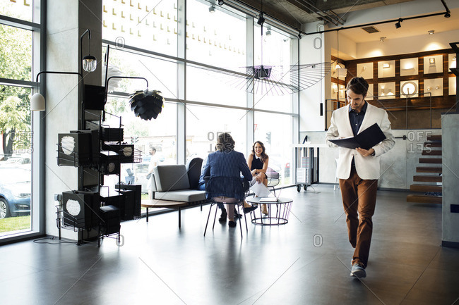 Businessman reading file while walking in office by colleagues in background