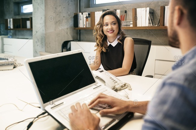 Smiling businesswoman looking at male colleague in office