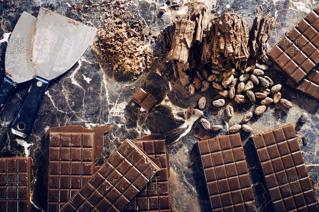 Overhead view of chocolate bars with nuts and kitchen knife on table