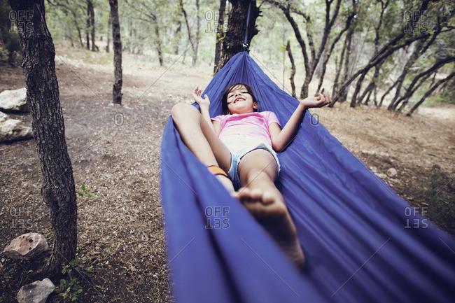 Girl lying on hammock in forest