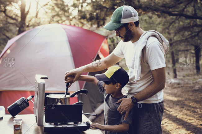 Father and son preparing food on camping stove in forest