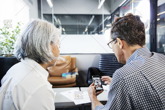 Businessman showing mobile phone to woman in office