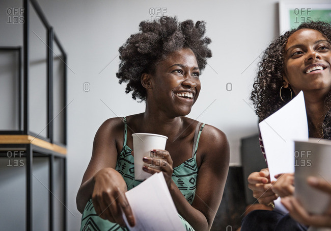 Happy colleagues holding drink and documents in office
