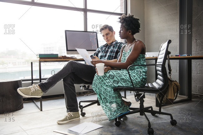 Colleagues discussing reports while sitting on office chair at desk