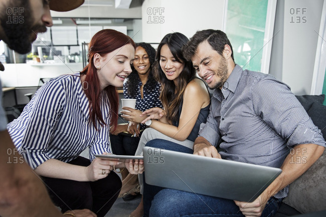 Man showing laptop computer to colleagues in office