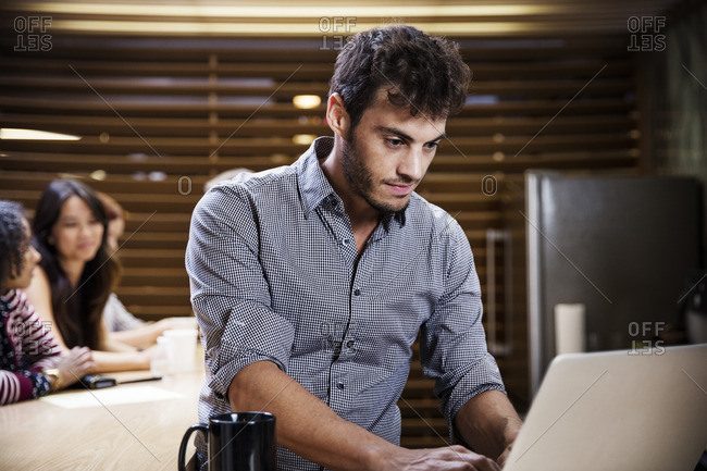 Man using laptop computer while sitting with colleagues in office