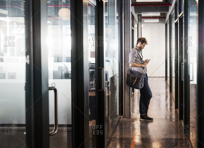 Man using mobile phone while leaning in office lobby