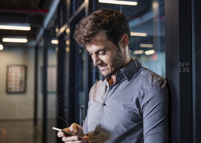 Happy man using mobile phone in office lobby