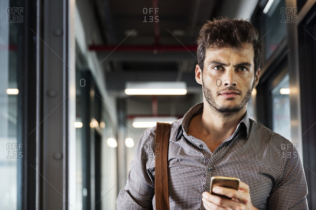Man looking away while holding mobile phone in office lobby