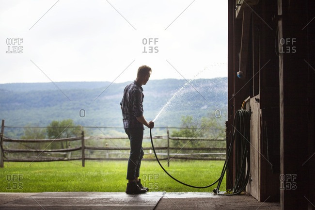 Rancher watering grass from fence while standing at stable entrance