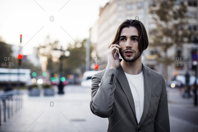 Businessman talking on mobile phone while standing on footpath in city