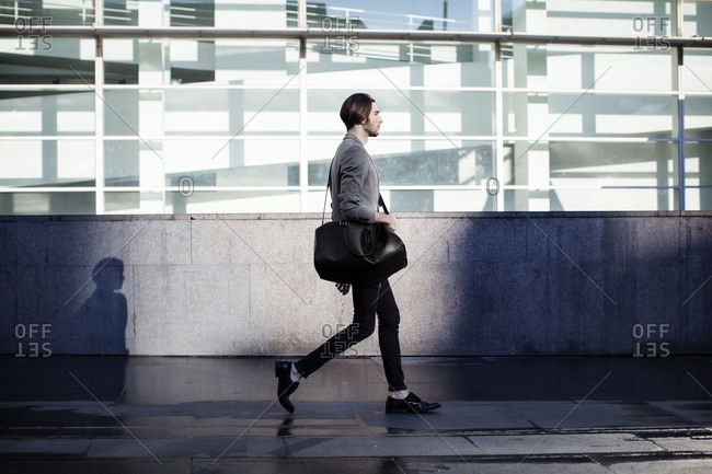 Businessman carrying bag and walking in office corridor