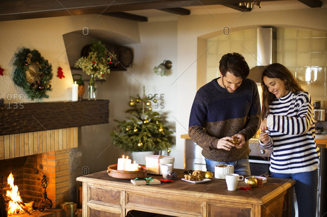 Smiling couple decorating home during Christmas