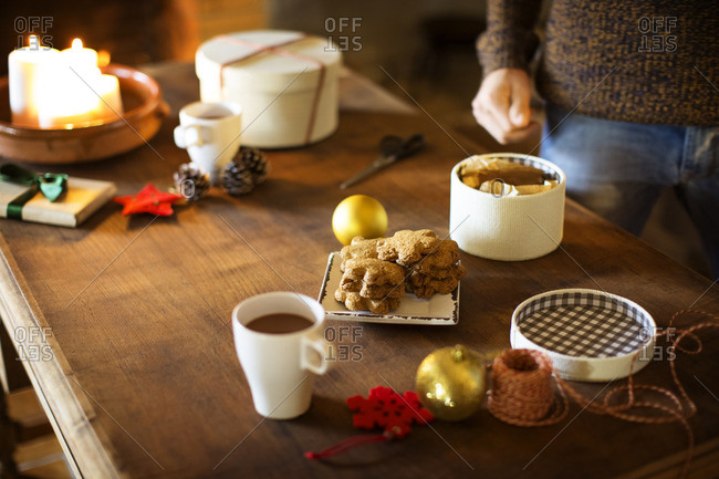 Cropped image of man preparing gift box while having cookies and coffee at table