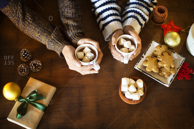 Cropped image of couple having marshmallow coffee with cookies at table