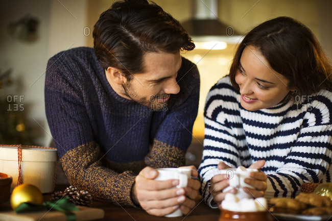 Smiling couple having coffee marshmallow at table during Christmas