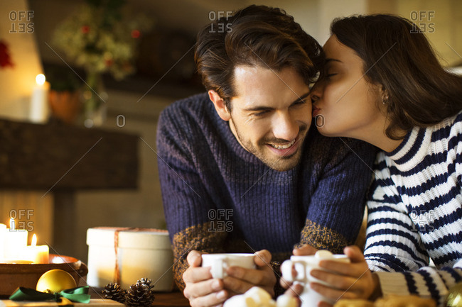 Woman kissing smiling boyfriend while having coffee at table during Christmas