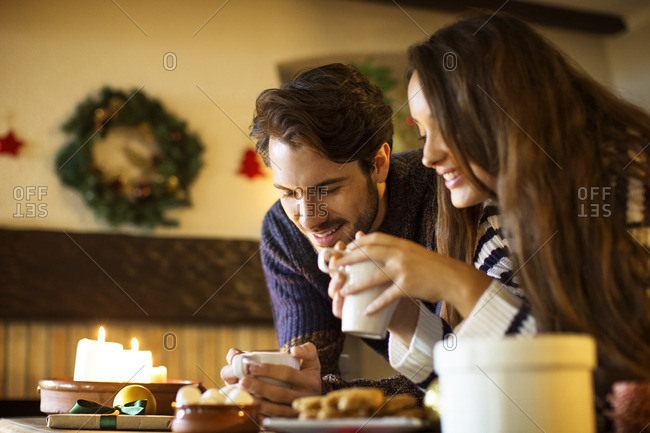 Smiling couple having coffee at table during Christmas
