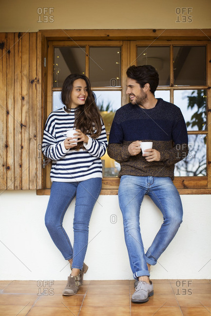 Smiling couple having coffee while standing against window on porch