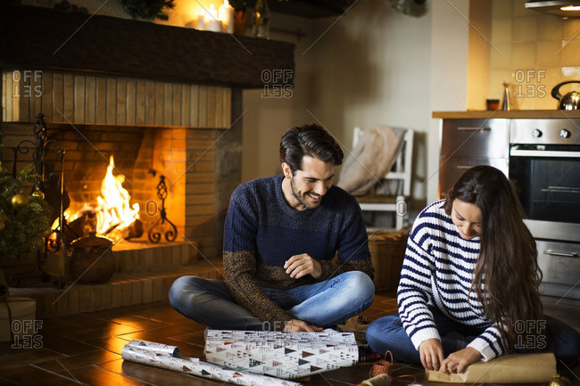 Happy couple wrapping gift boxes on floor by fireplace at home