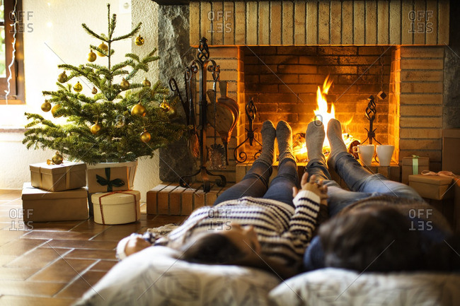 Couple holding hands resting by fireplace at home