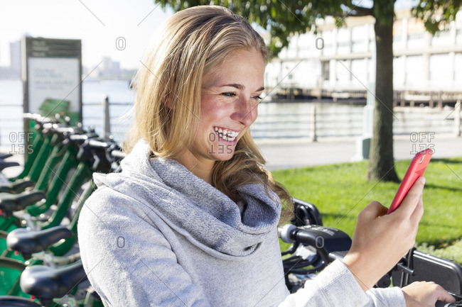 Cheerful woman using phone while standing against bicycle rack in city