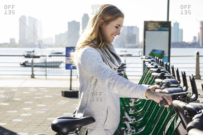 Side view of smiling young woman renting bicycle by lake in city