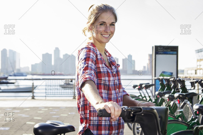 Portrait of confident smiling woman renting bicycle by lake in city
