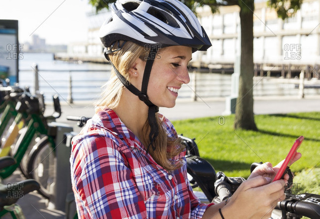 Woman wearing helmet using phone while standing against bicycle rack in city