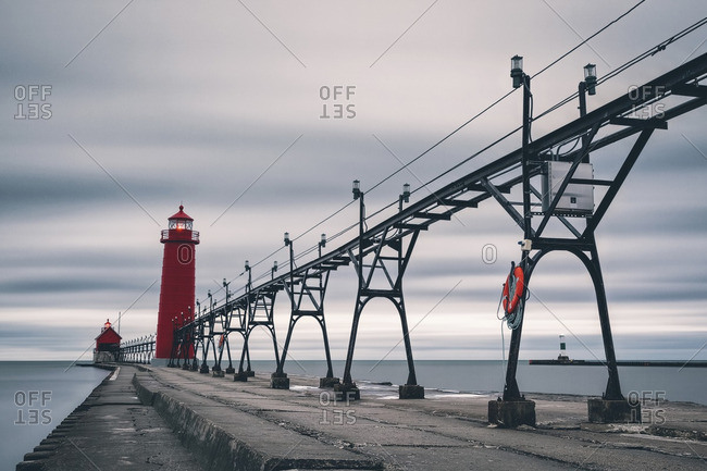 Electricity pylons and lighthouse on pier amidst sea against cloudy sky
