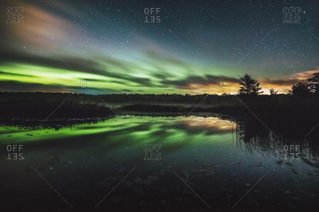 Reflection of aurora borealis on calm lake at night
