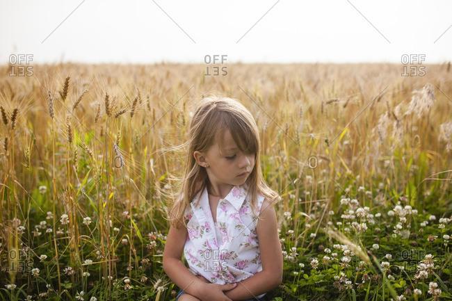 Upset girl sitting on field against sky in farm
