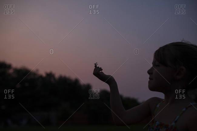 Girl with insect on finger standing against clear sky during sunset