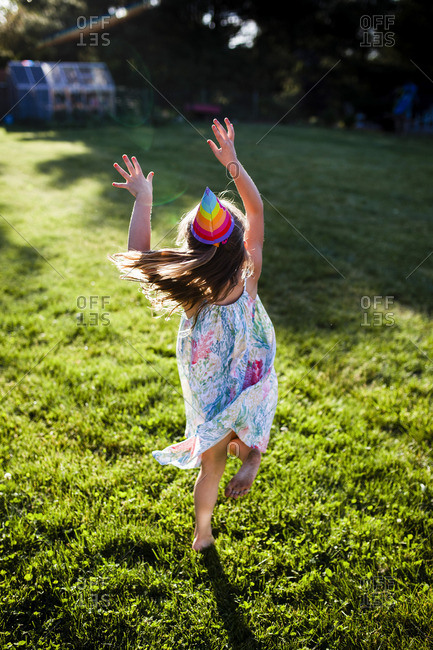 Cheerful girl in party hat jumping on grassy field at backyard