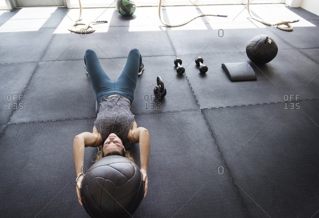 Focused athlete exercising with medicine ball in gym