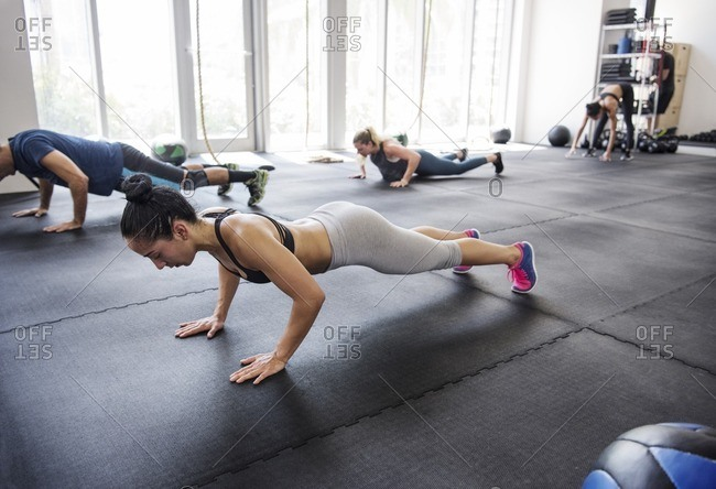 Determined athletes doing push-ups in brightly lit gym