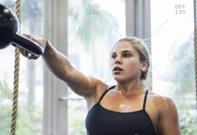 Determined athlete exercising with kettle bell in gym