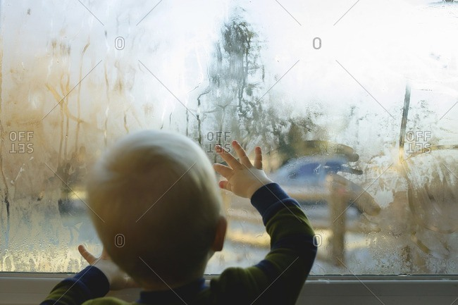 Rear view of boy looking through condensed glass window