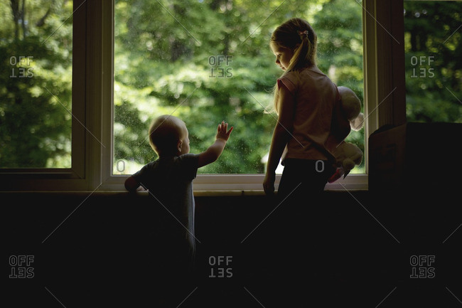 Girl looking at brother while standing by window