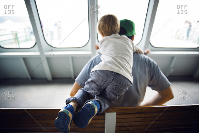 Rear view father and son traveling in a ferry
