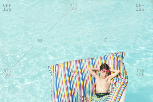 High angle view of boy lying on inflatable raft in swimming pool